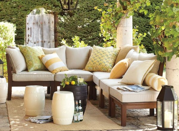 modern-home-pottery-barn-outdoor-furniture-decor-with-ivory-accents-pillows-and-cushions-also-vintage-candle-lights-and-cylinder-table-on-green-garden