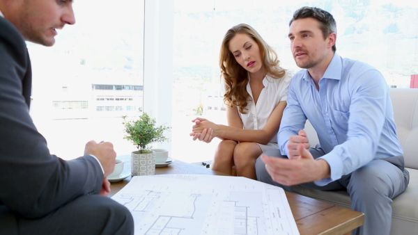stock-footage-couple-talking-to-their-architect-at-home-on-couch (1)