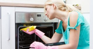 Young woman cleaning oven in the kitchen