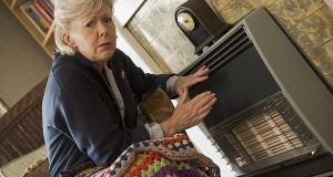 Woman warming herself by heater