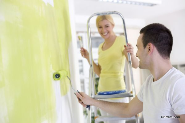 Cheerful couple  painting wall