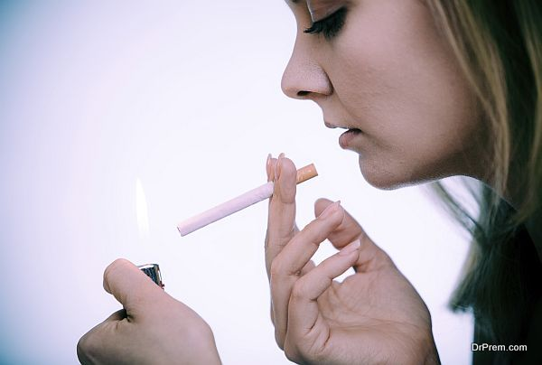 Young woman with lighter lighting up cigarette. Girl smoking.
