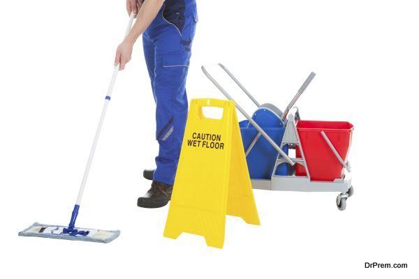 Low Section Of Servant Mopping Floor By Wet Floor Sign