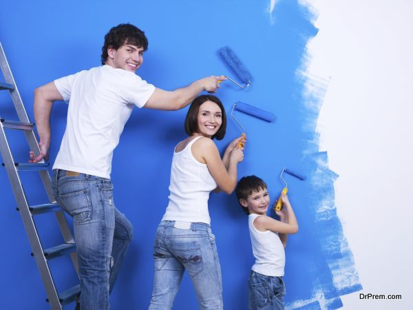 Happy young family with little son painting the wall