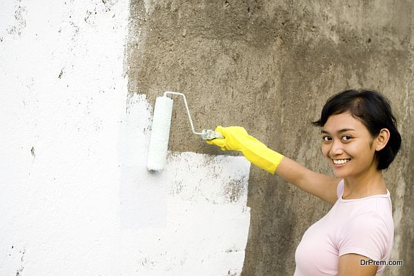 independent asian young woman painting exterior wall of her house with a white colored paint, using a roller and gloves on hands