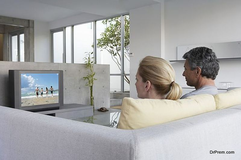 Couple relaxing on sofa watching television, rear view