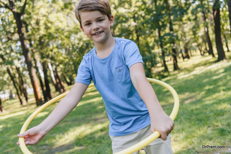 boy holding hula hoops