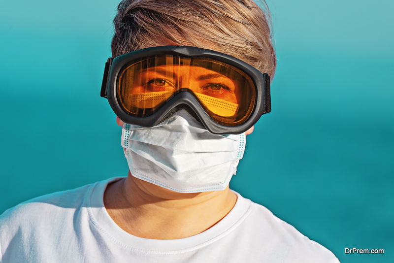 Woman in protective goggles and surgical face mask