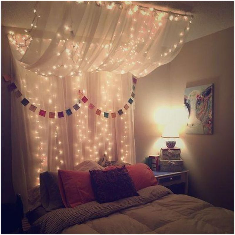 Queen-sized bed with hanging lights and canopy